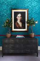 A striking portrait painting hangs on a turquoise blue wall above a rustic style chest of drawers in a stylish arrangement