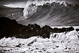 USA, Hawaii, Oahu, a surfer dropping in on a large wave at Waimea Bay, the North Shore (B&W)