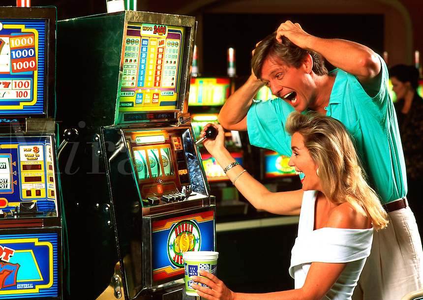 Excited couple playing slot machine