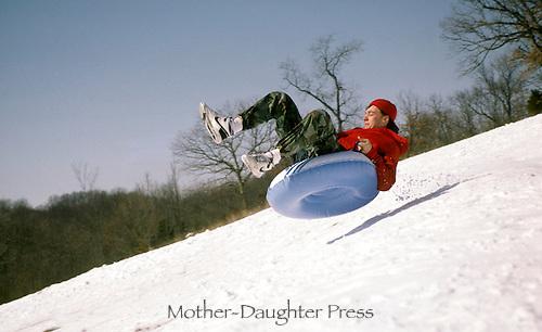 Teenaged boy takes on air while tubing down steep hill riding an inner tube.