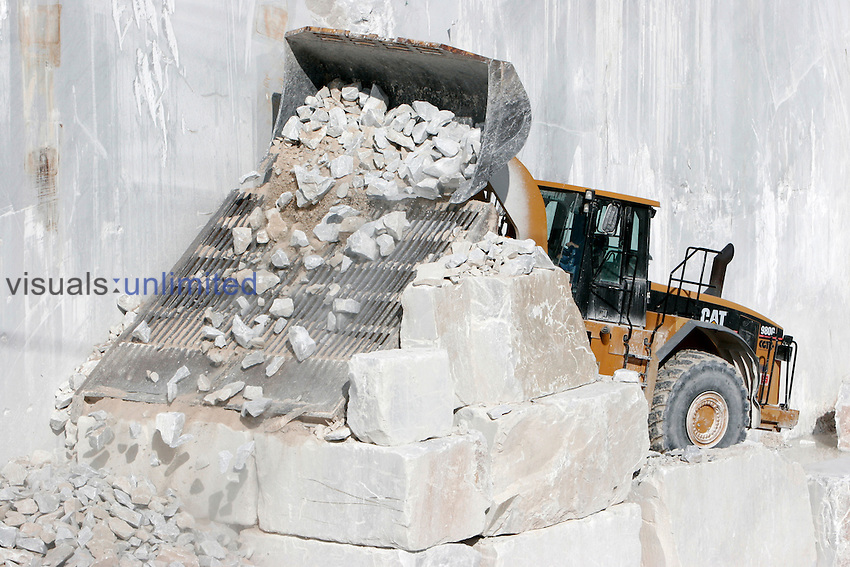 Miner in tractor sorting rock and soil in sifter in marble quarry, Carrara, Alpi Apuane, Italy