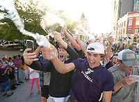 NWA Democrat-Gazette/ANDY SHUPE<br /> Kade Tune (left) and Jeff Sinacore join the rest of the Fayetteville High School baseball team Wednesday, Oct. 3, 2018, in spraying water and cheering during the school's annual homecoming parade on the city's downtown square. Fayetteville High plays Van Buren at 7 p.m. Friday at Harmon Stadium. Visit nwadg.com/photos to see more photographs from the parade.