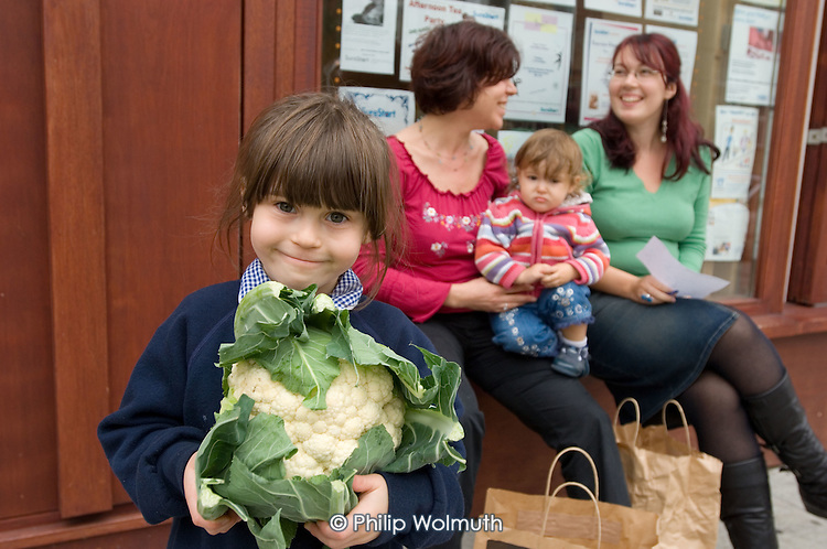 Queens Park Sure Start Farmer's Choice organic fruit and vegetable scheme: local mother Robyn Matheson talks to Sure Start worker Nina, while daughter Madeline holds a cauliflower.