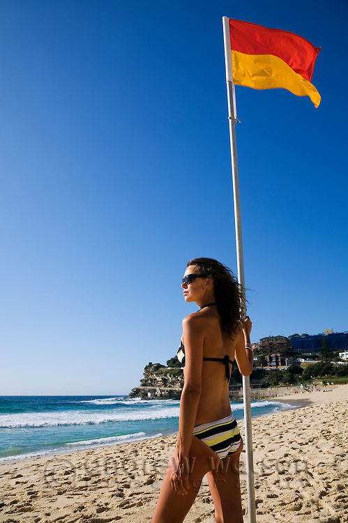Young woman on Bronte Beach with yellow and red surf lifesaving flag.  Sydney, New South Wales, AUSTRALIA.