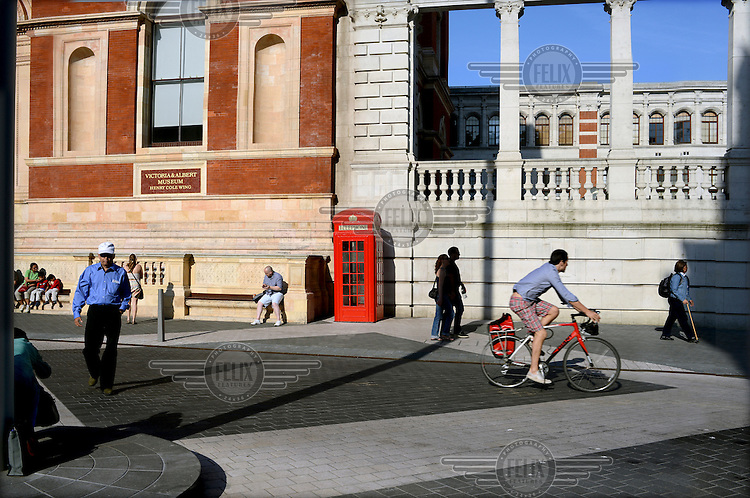 People using a newly pedestrianised area that links the museums of South Kensington, London. In the centre a bright red phone box has been positioned outside the Victoria and Albert Museum.