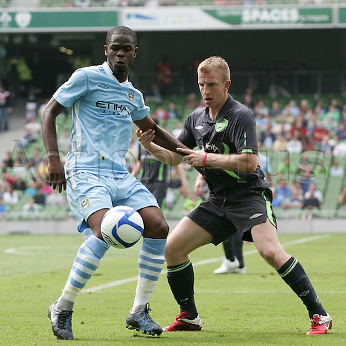 30.07.2011 Dublin Super Cup from the Aviva Stadium. Airtricity XI v Manchester City. Abdul Rzak (Manchester City) and Danny Murphy (Airtricity XI) in action.