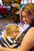 A mother her little boy who is about 28 months old, at a sling meet held in the family restaurant and play area in a pub.