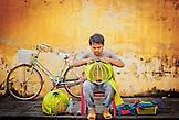 VIETNAM, Hanoi, a man sitting outdoors making a yellow paper lantern