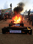 Palestinian Islamic Jihad activists burn mock coffins symbolizing Arab countries and other organizations they say did not help them during and after the war with Israel, at a rally marking the first anniversary of Gaza war, in Gaza city, Thursday, Dec. 31, 2009. Israel launched the three-week long offensive on Dec. 27, 2008, to end years of rocket fire from Gaza toward Israeli border towns. About 1,400 Palestinians were killed, including hundreds of civilians, along with 13 Israelis. Photo by Mohammed Othman