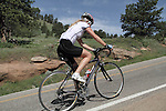 Woman with blond hair bike riding up Flagstaff Mountain, Boulder, Colorado. .  John offers private photo tours in Denver, Boulder and throughout Colorado. Year-round.