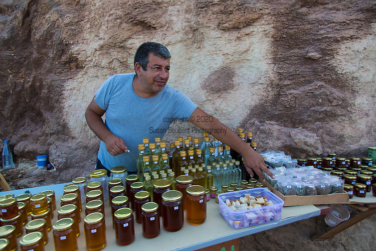 A local man selling traditional Cretan products such as honey, olives with almonds, small bottles of home made wine and raki, along the road during the scenic drive to  Balos Beach on the Gramvousa Peninsula, Crete, Greece