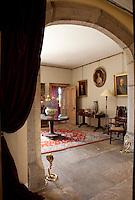 The spacious entrance hall is furnished with family relics and portraits, each with a story to tell