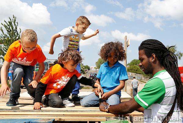 Nederland Amsterdam  2015 06 10 . Landelijke Buitenspeeldag. Honderden kinderen spelen buiten op het NDSM terrein. Vader helpt zoon en vriendjes met het bouwen van een hut