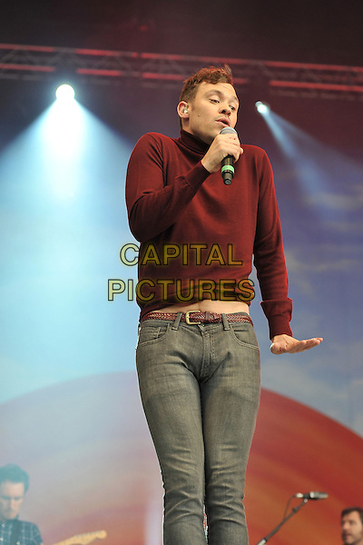 Will Young.At BBC Radio 2 Live in Hyde Park, London, England..September 11th, 2011.stage concert live gig performance music half length 3/4 singing red maroon burgundy top sweater jumper grey gray jeans denim belly stomach midriff funny.CAP/MAR.© Martin Harris/Capital Pictures.