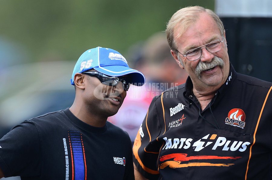 Sept. 15, 2012; Concord, NC, USA: NHRA top fuel dragster driver Antron Brown (left) talks with crew chief for top fuel dragster driver Clay Millican during qualifying for the O'Reilly Auto Parts Nationals at zMax Dragway. Mandatory Credit: Mark J. Rebilas-