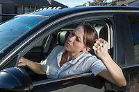Beautiful young business woman driver shakes her fist out car window while stuck in Austin traffic.