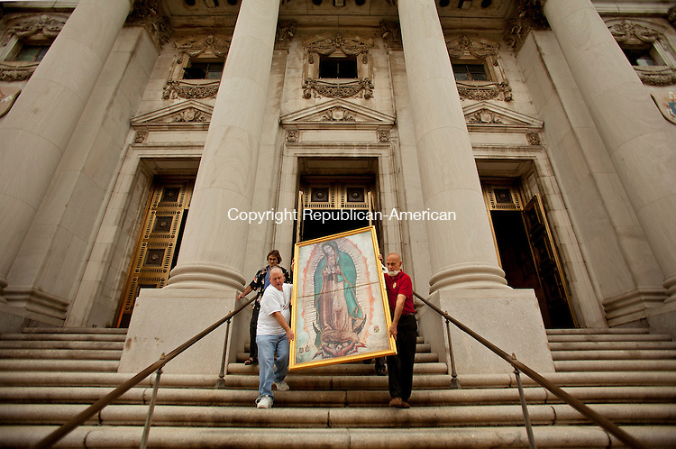 WATERBURY, CT-10 September 2013-091013BF01- Peter Harkins, left, from Watertown and Greg Bailey, right, from The Knights of Columbus, along with Sal Paradiso, rear, from California, carefully move a digital replica, exact in size and color to the original Santa Maria de Guadalupe that appeared on the cactus fiber cloak of Juan Diego in 1531, down the front steps of the Basilica of the Immaculate Conception in Waterbury Tuesday morning. The image led a procession of about 35 people from the Basilica to Planned Parenthood where they prayed the Rosary in protest against abortion. The Knights of Columbus organized the protest. Bob Falcetti Republican-American