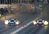 Jul. 18, 2014; Morrison, CO, USA; NHRA funny car driver Tim Wilkerson (right) races alongside Jack Beckman during qualifying for the Mile High Nationals at Bandimere Speedway. Mandatory Credit: Mark J. Rebilas-