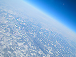 Aerial view from airplane of frozen, snow covered earth.