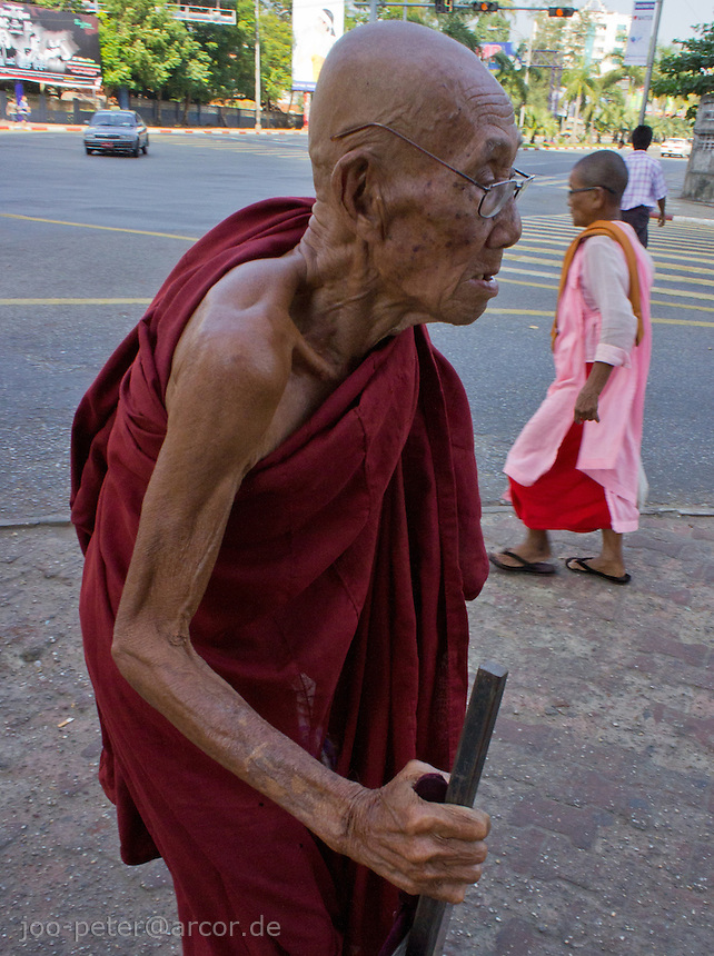 Old monk in Yangon, nun walking by in the background