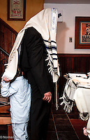 "Father of new born daughter conducts her naming ceremony (called ""brit bat"") in private synagogue. Young son plays hide and seek behind tallis."