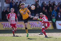 Romuald Boco of Accrington Stanley shoots at goal under pressure from Jake Gosling of Newport County during the Sky Bet League 2 match between Newport County and Accrington Stanley at Rodney Parade, Newport, Wales on 28 March 2016. Photo by Mark  Hawkins.
