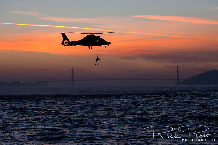 A Coast Guard HH-65 Dolphin helicopter lifts a rescue swimmer out of the waters of San Francisco Bay at sunset. The helicopter and crew, based at U.S. Coast Guard Air Station San Francisco, was on a practice mission to maintain qualifications and search and rescue proficiency.