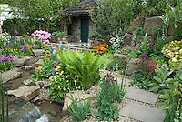 Beautiful spring garden with ferns, house, waterfall, stream water feature, trees, rocks, azalea, rhododendron, hosta, many colors, colorful, primula, aquilegia, stone wall, patio, pathway