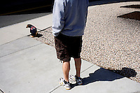 A man walks a dog wearing a Boston Red Sox jersey on the day of the 2011 season opener in Boston, Massachusetts, USA.