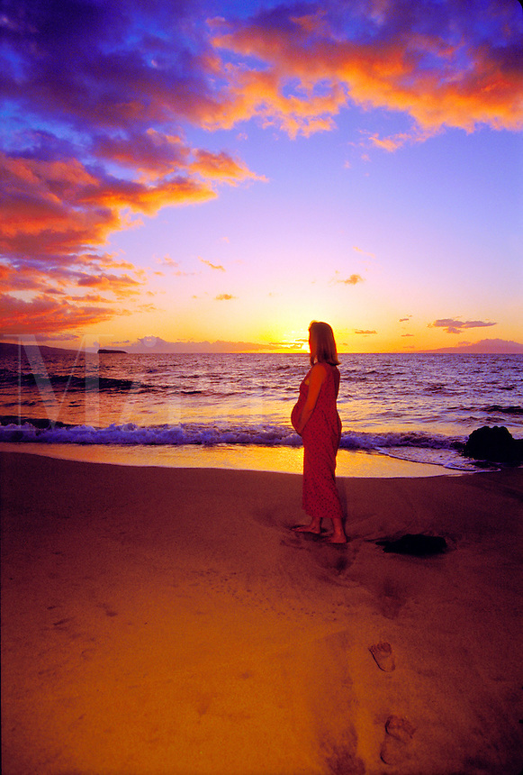 Expectant mother in profile as she walks on a beach at sunset. Maui, Hawaii.
