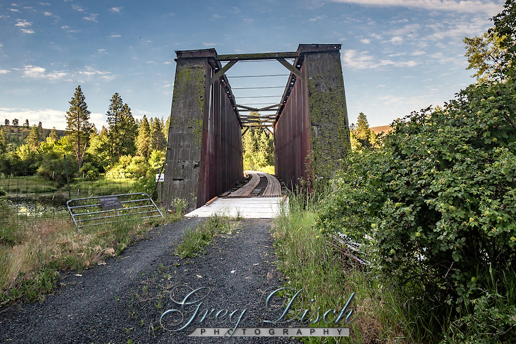 The Manning-Rye Covered Bridge crosses the Palouse River outside of Colfax. It was constructed about 1918 by the Spokane and Inland Empire Railroad, an expansive interurban electric railroad line scheme that extended from the Palouse to Spokane. In contrast to most railroads, the electric railways could provide a frequent, rapid service with numerous stops. <br /> <br /> Because it was most feasible to construct the electric railroads in well developed areas, the promoters focused on areas like the Palouse, rather than on areas that had no railroad service at all. By the summer of 1907, the electric line to Colfax was completed. Presumably, the Manning-Rye Covered Bridge replaced the original structure constructed over the Palouse River in 1907. The timber housing protects a single span timber Howe truss which rests on timber pile abutments, encased with timber cribs. Because it was necessary to provide for the connection between the locomotive and the overhead electric lines, the top of the bridge was left uncovered.  There are doors in the housing to provide access for the maintenance of the truss components. <br /> <br /> The bridge eventually became the property of the Great Northern Railroad, and subsequently was owned by the Norther Pacific Railroad; it remained in use as a railroad bridge until 1967. In 1969 it was purchased by its present owner who saved the structure from demolition. At this time, the rails were replaced with wooden planking so that the present owner could use the structure for automobile access to her property. The Manning-Rye Bridge is one of four covered bridges remaining in Washington.<br /> <br /> The bridge was added the National Register of Historic Places July 15, 1982.