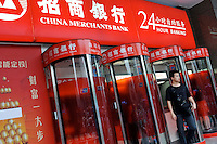 People withdraw money from ATM machines at China Merchants Bank in Guangzhou, China...