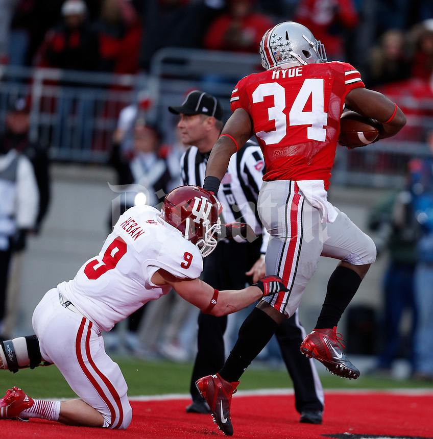 Ohio State Buckeyes running back Carlos Hyde (34) skips past Indiana Hoosiers safety Greg Heban (9) to score a touchdown late in the second quarter of Saturday's NCAA Division I football game against Indiana at Ohio Stadium in Columbus on November 23, 2013. (Barbara J. Perenic/The Columbus Dispatch)
