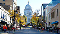 People walk and bike down State Street in front of the Wisconsin State Capitol Building on Saturday, October 17, 2015 in Madison, Wisconsin
