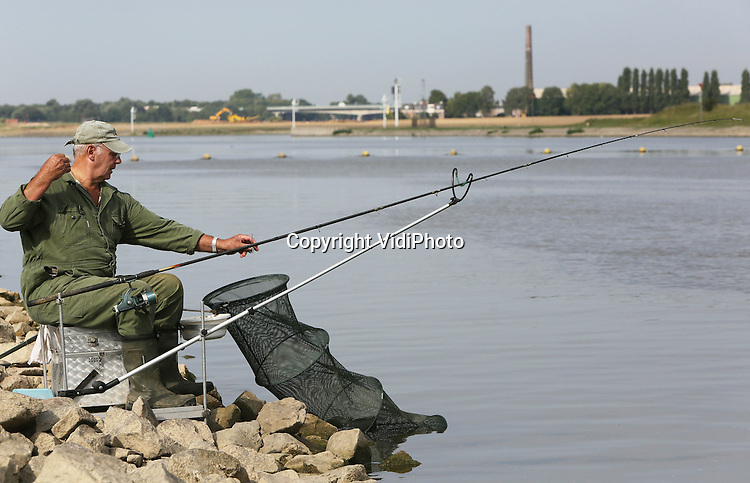 Foto: VidiPhoto<br /> <br /> DRIEL - Nu door de lage waterstand in de rivieren de deuren van de stuw in Driel gesloten is, is het een stuk rustiger vissen in de Neder-Rijn. De stroming is nu flink minder. Sportvissers maken bovendien dankbaar gebruik van de mogelijkheid nu dichter bij de diepere gedeelten van de rivier te kunnen vissen. Om te voorkomen dat het scheepvaartverkeer op de Boven-Rijn in de problemen komt, is de stuw bij Driel gesloten. De waterstand in de grote rivieren zakt nog steeds door de aanhoudende droogte van deze zomer. Sproeiverboden blijven voorlopig gehandhaafd. Waterschappen laten hier en daar extra water in om de stand in sloten en watergangen op peil te houden