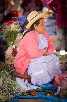 Quechua woman selling various vegetables and flowers at Chinchero Town Sunday Market, Cusco region, Peru, South America
