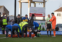 Goalkeeper James McKeown of Grimsby Town asked questions of Referee Nick Kinseley as Gavin Gunning of Grimsby Town lays injured following a clash of heads during the Sky Bet League 2 match between Grimsby Town and Wycombe Wanderers at Blundell Park, Cleethorpes, England on 4 March 2017. Photo by Andy Rowland / PRiME Media Images.