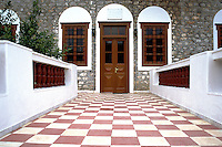 "Entrance with an interesting pattern and symmetry in Hydra one of the Saronic Islands of Greece, located in the Aegean Sea between the Saronic Gulf and the Argolic Gulf. It is separated from the Peloponnese by narrow strip of water. In ancient times, the island was known as Hydrea which was a reference to the springs on the island...The municipality Hydra consists of the islands Hydra (area 50 km2), Dokos (pop. 13, area 12.5 km2) and a few uninhabited islets...There is one main town, known simply as ""Hydra port"" (pop. 2,526 in 2001). It consists of a crescent-shaped harbor, around which is centered a strand of restaurants, shops, markets, and galleries that cater to tourists and locals (Hydriots). Steep stone streets lead up and outwards from the harbor area. Most of the local residences, as well as the hostelries on the island are located on these streets. Other small villages or hamlets on the island include Mandraki (pop. 33), Kamini, Vlychos (28), Palamidas (18), Episkopi, and Molos."