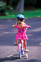 Little girl, wearing protective helmet, learning to ride a bike with training wheels