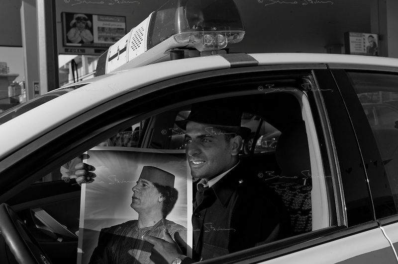 Tripoli, Libya, March 27, 2011..A policeman waitng for his patrol car to be filled up at a petrol station.The embargo against Libya is starting to take a toll on the economy, the most visible sign being the long queues at the rare petrol stations still open.