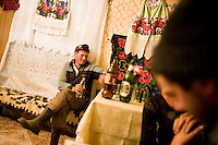 ROMANIA / Maramures / Mara / 18.10.2006 ..Drinking in Mara village. A peasant opens a bottle of homemade 110 proof plum brandy, the ultra strong national drink. ..© Davin Ellicson / Anzenberger