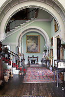 Inside the house on the Clandeboye estate, which is the home to Lady Dufferin, Marchioness of Dufferin and Ava. The staircase, flanked by a pair of Icelandic narwhal tusks and decorated with artefacts collected in East Asia, all souvenirs from travels by the 1st Marquess.