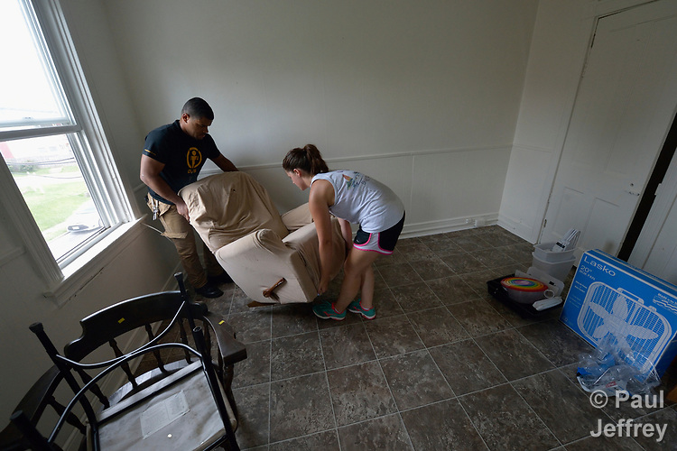 Luis Ortiz and Emilie MacDonald move a chair into an apartment in Lancaster, Pennsylvania. They are furnishing what will become home for a refugee family about to arrive in the United States. The two work for Church World Service, which resettles refugees in Pennsylvania and other locations in the United States. <br /> <br /> Photo by Paul Jeffrey for Church World Service.