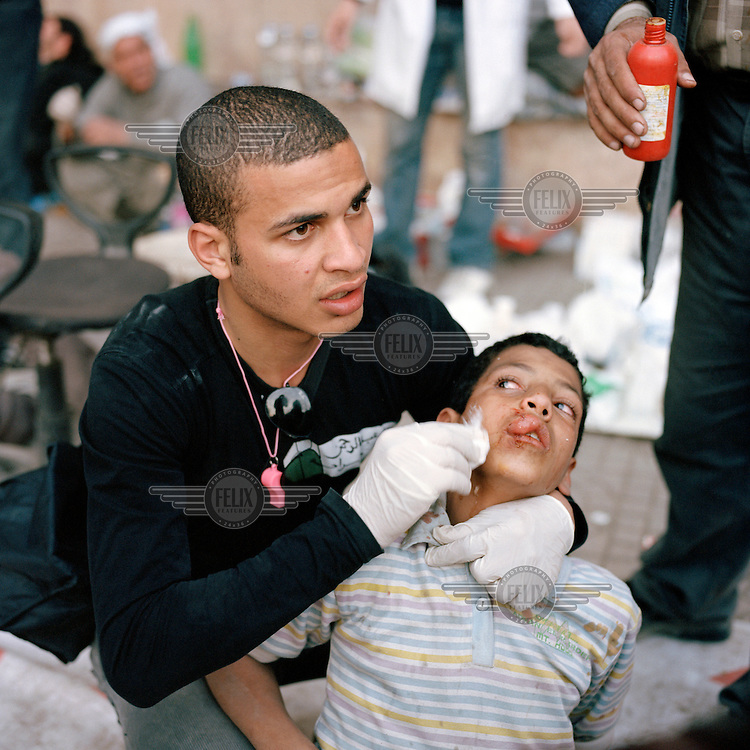 A volunteer medic in Tahrir Square treats a young boy who was allegedly caught while fighting for supporters of Mubarak. Although badly stunned by a stone that hit him in the face, when the boy came to  he was terrified to find he had been captured and was eager to get away from the people who were trying to help him. 25 January 2011 saw the beginning of a nationwide 18 day protest movement that eventually ended the 30-year rule of Hosni Mubarak and his National Democratic Party. .