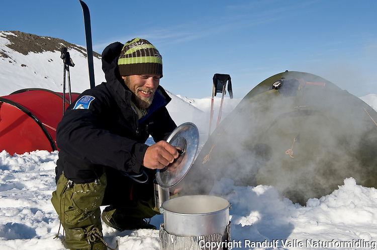Mann smelter snø i teltleir. --- Man melting snow in camp.