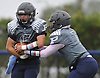 Plainview JFK running back No. 15 Nico Mueller, left, takes a handoff from quarterback No. 7 Kevin Pastier during a Nassau County Conference I varsity football game against Port Washington at Plainview JFK High School on Saturday, October 3, 2015. Mueller ran for four touchdowns in the first half to lead the Hawks to a 42-0 win.<br /> <br /> James Escher