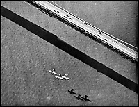 BNPS.co.uk (01202 558833)Pic: CharterhouseAuctioneers/BNPS<br /> <br /> Three Swordfish biplane's flying over the Bay Bridge, California.<br /> <br /> A remarkable wartime photo album that highlights the perilous nature of landing a fighter plane on an aircraft carrier in heavy seas has been unearthed.<br /> <br /> The black and white snaps show several Royal Naval aircraft coming a cropper while attempting to land on board HMS Fencer often in heavy seas.<br /> <br /> One set of images depict a Swordfish biplane crashing into the sea a few hundred yards off the aircraft carrier HMS Fencer.<br /> <br /> Other photos show a Supermarine Seafire about the crash into the superstructure.<br /> <br /> The album will be sold by Charterhouse Auctioneers in Sherborne, Dorset.