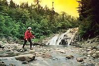 Hiker navigating riverbed and waterfall, Mary Ann Falls, Cape Breton Highlands National Park, Nova Scotia, Canada