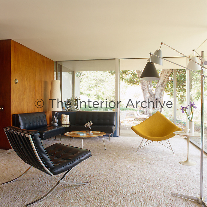 This contemporary living room is furnished with retro designer chairs and lamps