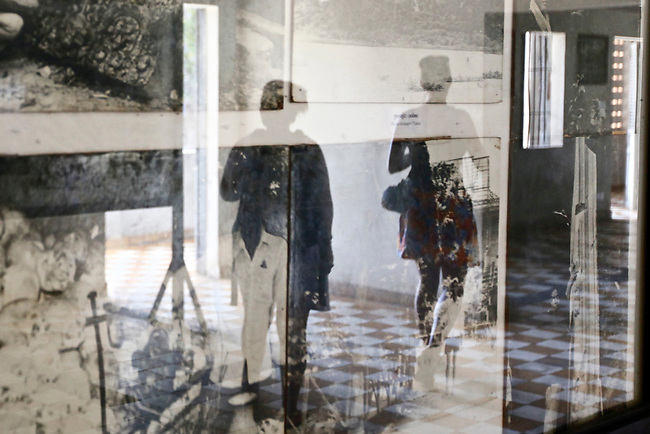 The image of two visitors is reflected in the glass of a display case containing photos of the Khmer Rouge regime at Tuol Sleng prison in Phnom Penh, Cambodia. More than 500 people visit the prison, now called the Tuol Sleng Genocidal Museum, each day. March 1, 2012.